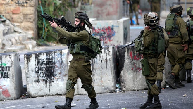 Israeli soldiers take up position during clashes with Palestinian protesters in the West Bank city of Hebron, October 19, 2015.