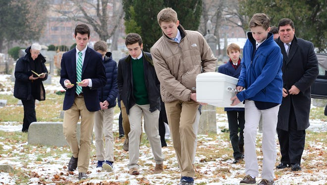 John Manahan and Finn Gannon carry the casket to the gravesite for the funeral services of a stillborn baby found abandoned in a Mine Hill recycling center in October.