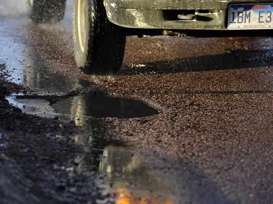 Drivers avoid potholes along Louise Avenue in western Sioux Falls. A winter defined by extreme cold snaps broken up by a few stretches in which temperatures have poked above freezing can create the potential for a severe pothole season.