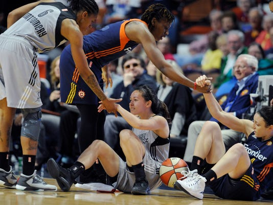 San Antonio Stars' Kelsey Minato, bottom center, receives a helping hand from teammate Alex Montgomery, left, as Connecticut Sun's Brandie Baker helps up Sun's Connecticut Sun's Kelly Faris during the first half of a WNBA basketball game, Thursday, May 5, 2016, in Uncasville, Conn. (AP Photo/Jessica Hill)