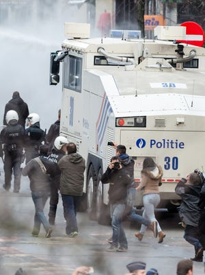 Police use a water canon as right wing demonstrators protest at a memorial site at the Place de la Bourse in Brussels on March 27, 2016.