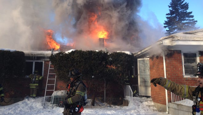 Firefighters work to extinguish a Chestnut Ridge house blaze that engulfed the one-story home Monday morning.