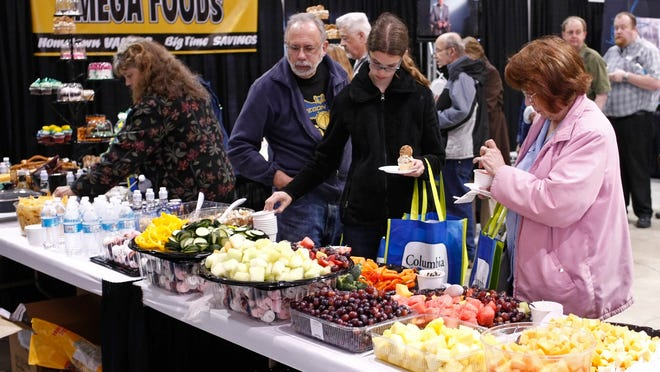 People enjoy the samplings of food available at the Mega Food booth during the annual Showbiz trade show on Thursday. People enjoy the samplings of food available at the Mega Food booth during the annual Showbiz trade show at the AmeriCraft Center, at the Oregon State Fairgrounds, on Thursday, May 8, 2014.