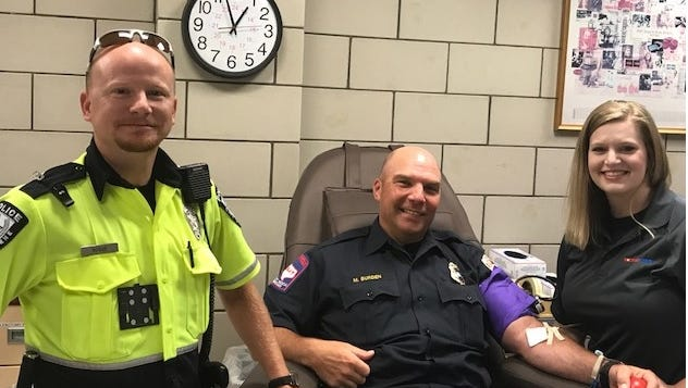 Abilene Deputy Fire Chief Michael Burden donates during the Guns and Hoses blood drive while Abilene Police traffic officer Jeff Hogue and MetroCare EMT Kasi Hutcherson wait.