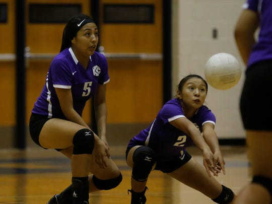 Kirtland Central's Tiana Aspaas returns a serve, next to Bioncee Yazzie during a Sept. 11, 2015, game at Jerry A Conner Fieldhouse in Farmington.