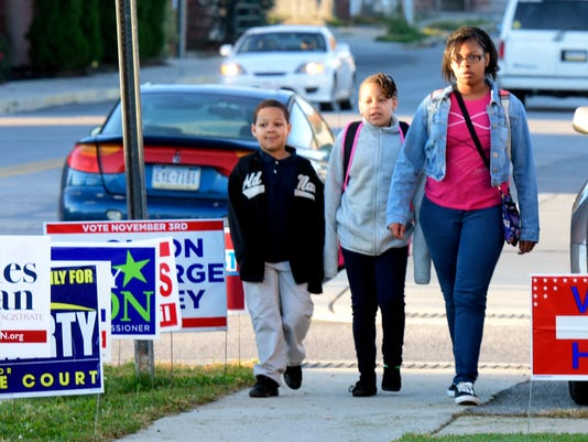 Devers K-8 students, from left, Johnny Dickerson, 6; Sheliyah Orr, 9, and A'naya Perry, 12, walk to school past political signs at the Lincoln Engine Co. polling place on Election Day last week. Local turnout in that election was about 20 percent.