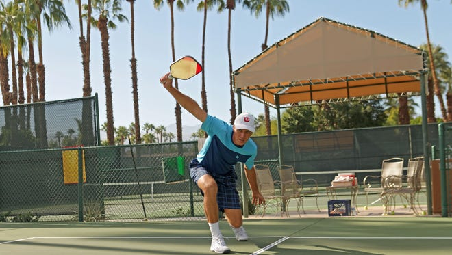 Marcin Rozpedski demonstrates proper pickleball form during an interview at The Lakes Country Club in Palm Desert, Tuesday, November 24, 2015.