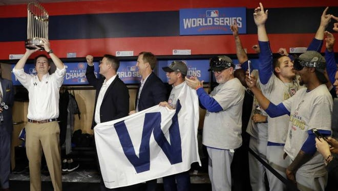 Chicago Cubs owner Tom Ricketts hoists the commissioner's trophy after Game 7 of the World Series against the Cleveland Indians in the Progressive Field locker room.