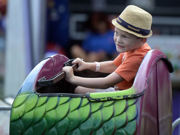 Jericho Powell, 5, rides a little rollercoaster at the Preble County Fair Friday, Aug. 1, 2014, in Eaton, Ohio.