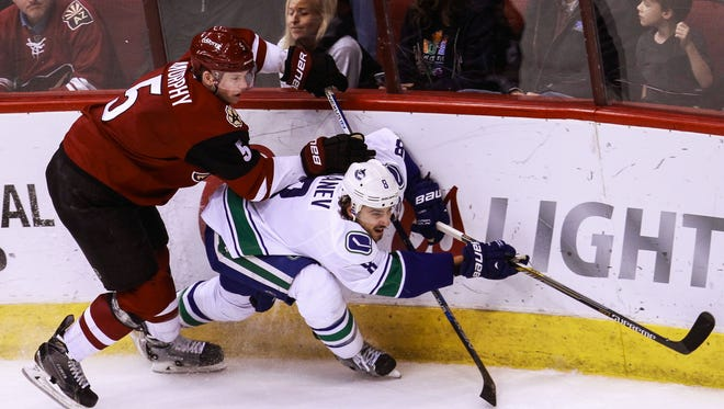 Arizona Coyotes' Connor Murphy and Vancouver Canucks' Christopher Tanev collide as the Arizona Coyotes face off against the Vancouver Canucks on Wednesday, Feb. 10, 2016, at Gila River Arena in Glendale, Ariz. Canucks beat the Coyotes 2-1.