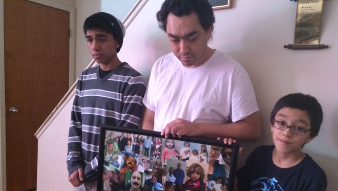Sam Monroy Sr. holds a collage of family photos with his son Sam Monroy Jr., left, and Nicholas, right at his South Lansing home Feb. 27, 2016.