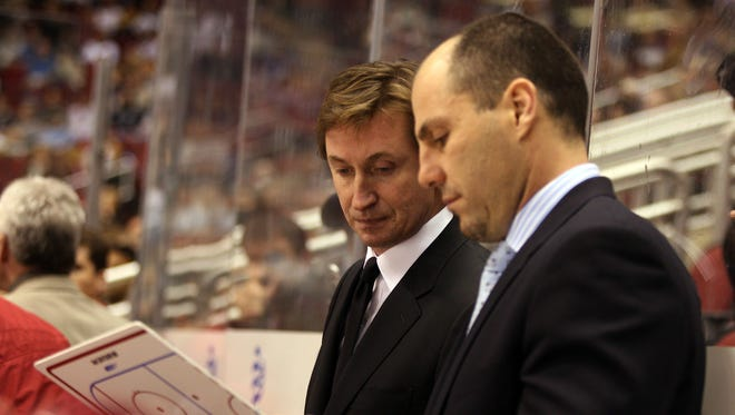 Phoenix Coyotes head coach Wayne Gretzky goes over the play with associate coach Rick Tocchet during the third period against the Los Angeles Kings at Glendale Arena in 2006.