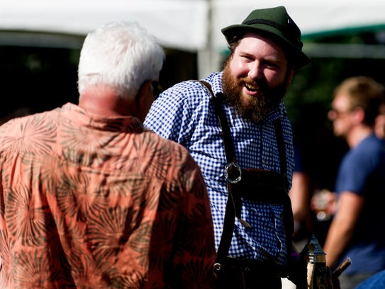 An attendee wearing lederhosen chats at the 21st annual