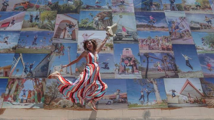 Artist Eyoalha Baker jumps in front of her mural made