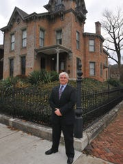 Matt Stegall poses outside his home at 326 N. 10th St. in 2013. Rehabilitating the home, which had been condemned in 1988, was part of Stegall's plan for rejuvenating the neighborhood where his business is located. He's been working on neighborhood restoration ever since.