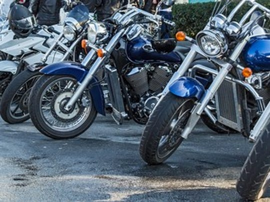 Line of motorcycles parked on a paved surface.