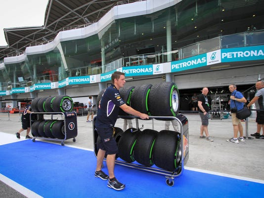A Red Bull pit staff member pushes sets of tires in the paddock ahead of the Malaysian Formula One Grand Prix at Sepang International Circuit in Sepang, Malaysia, Thursday, March 27, 2014. (AP Photo/Peter Lim)