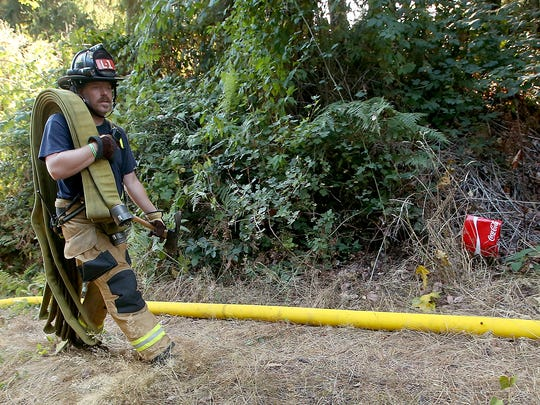 Bremerton firefighter Rob Smith carries hose down an access road as Bremerton and Central Kitsap crews  extinguish a brushfire off of Riddell Road in Illahee Preserve on Monday, September 11, 2017.
