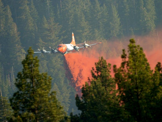 An air tanker drops almost to tree level to deliver