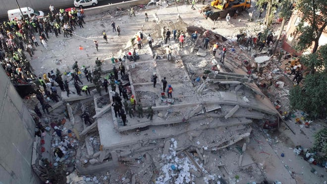 Rescuers look for survivors in a multistory building flattened by a powerful quake in Mexico City on Sept. 19, 2017.