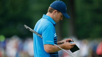 Jordan Spieth looks at his yardage book on the 14th hole during the first round of the 2016 PGA Championship golf tournament at Baltusrol.