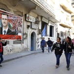 School students walk past a poster of Syrian President Bashar Assad in the old city of Homs on Tuesday.