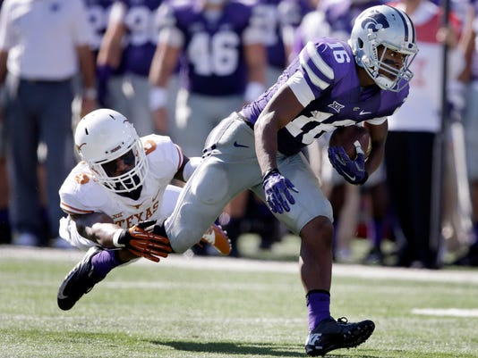 Kansas State wide receiver Tyler Lockett (16) breaks a tackle by Texas cornerback Quandre Diggs (6) during the second half of an NCAA college football game in Manhattan, Kan., Saturday, Oct. 25, 2014. Kansas State defeated Texas 23-0. (AP Photo/Orlin Wagner)