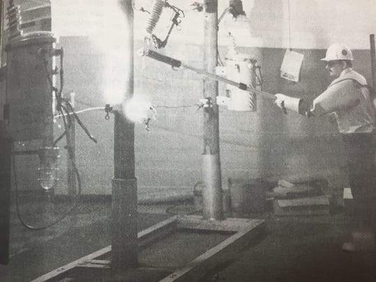 Ray Rubarts of the Kentucky Utilities Company used a pole to start a small electrical fire in March 1990. Rubarts and other KU employees demonstrated the danger of outdoor electrical wires to students of Morganfield Elementary students.