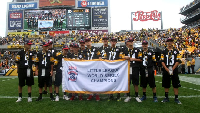 The Maine-Endwell Little League World Series-winning baseball team poses with their championship banner on Sunday. The team was honored during halftime of  the game between the Cincinnati Bengals and the Pittsburgh Steelers at Heinz Field.