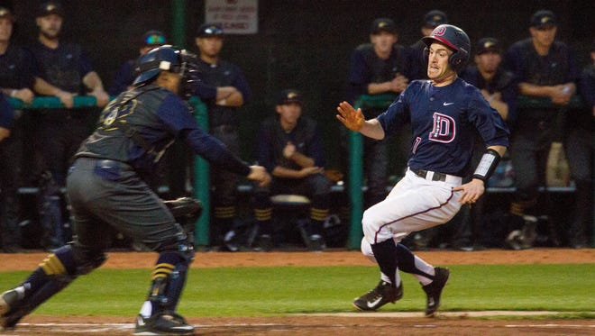 Dixie State shortstop Tanner Morache runs into home plate for a point against California Baptist Thursday, March 3, 2016.