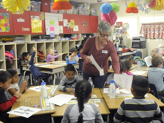 Joan Bagley hands out papers while volunteering at Yerington Elementary School.