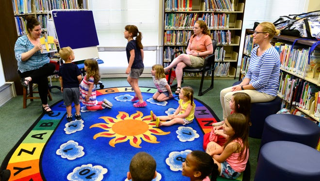 Jessica Haught, children's librarian at Birchard Public Library, reads during story time on Tuesday evening.