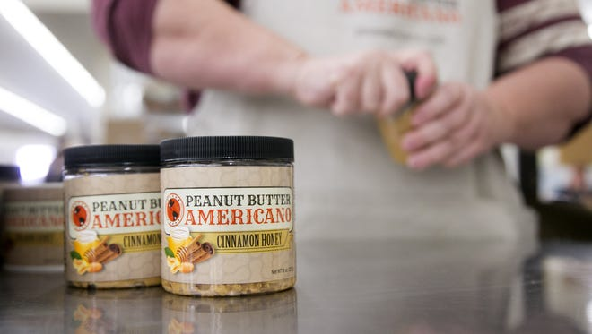 Kim McGrath, a production manager, puts labels on Peanut Butter Americano jars in Glendale.