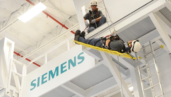 Siemens Energy wind trainers demonstrate a safety and rescue training simulation at Siemens Energy's wind service training center in Orlando, Fla.