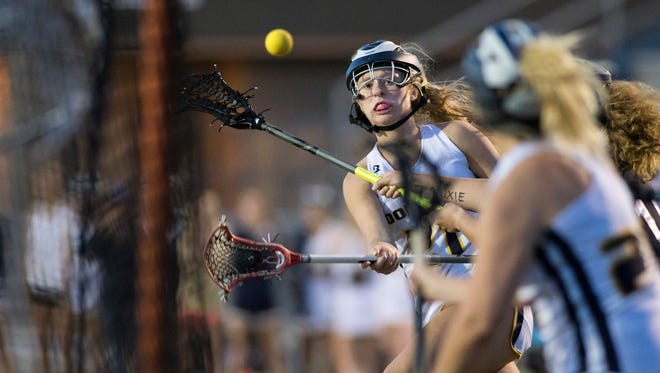 Dolphin Avery Currington (21) shoots and scores during the district 1 girls lacrosse championship game between Gulf Breeze and Pensacola High Schools at Gulf Breeze High School on Thursday, April 19, 2018.