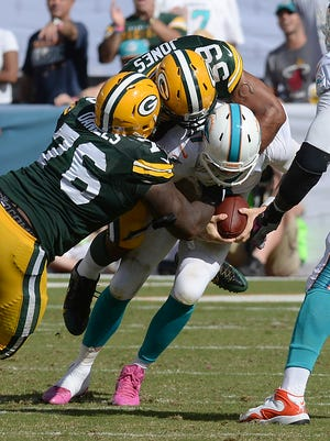 Green Bay Packers Mike Daniels (76) and Brad Jones (59) combine to sack quarterback Ryan Tannehill (17) against the Miami Dolphins at Sun Life Stadium.