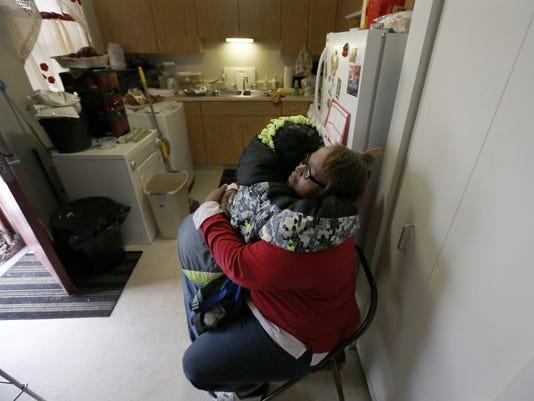 Debra Aldridge, right hugs and recites a prayer with her grandson Mario Hendricks
