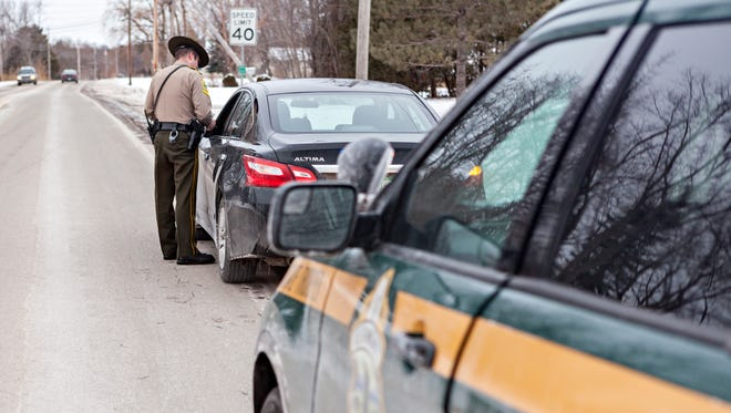 File: Vermont State trooper speaks with a driver.