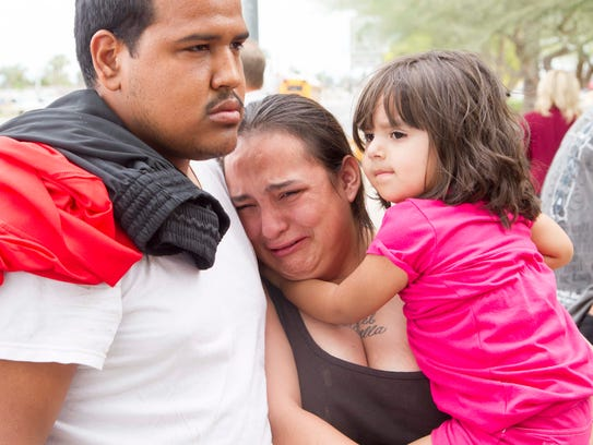Tanya Ehrig, 27, with her child Trinity, cries for