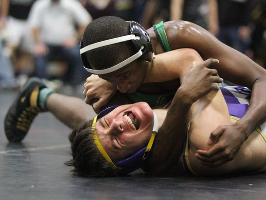 Lincoln's Anderson Stennett pins a his grimacing opponent