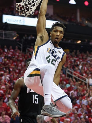 Utah Jazz guard Donovan Mitchell hangs from the rim after his dunk during the second half in Game 2 of an NBA basketball second-round playoff series against the Houston Rockets, Wednesday, May 2, 2018, in Houston.