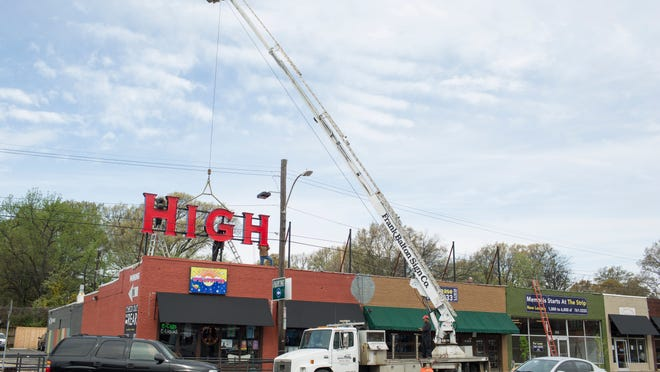 Workers from the Frank Balton Sign Company attach the first section of the new Highland Strip sign into place on Highland Avenue. The sign, at the intersection of Highland and Walker Avenue, also includes neon lights to make it glow during the evening.