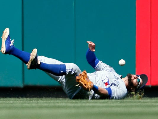 Toronto Blue Jays center fielder Kevin Pillar is unable to hold on to a double by St. Louis Cardinals' Dexter Fowler during the eighth inning in the first game of a baseball doubleheader Thursday, April 27, 2017, in St. Louis. (AP Photo/Jeff Roberson)