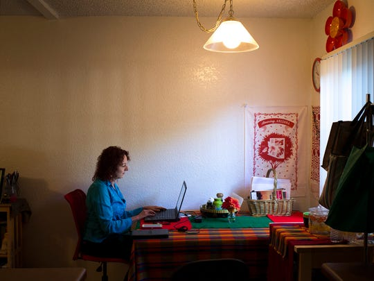 Laura Libman, president of the Tia Foundation, works on her computer in her Phoenix home on Sept. 29, 2014.