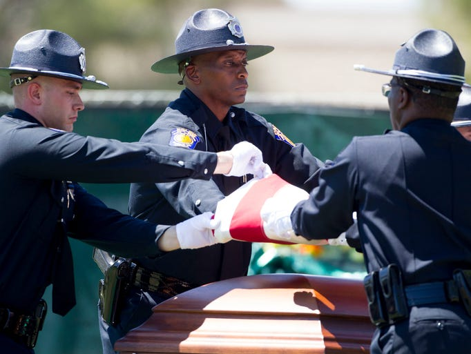 Salt River Police Department Honor Guard clockwise left Nicholas Azzano, Christopher Davis, and Eric Mitchell, right,  fold the flag from fallen Salt River police officer Jair Cabrera casket during services at Phoenix Memorial Park and Mortuary. Cabrera was shot in the head during a traffic stop.