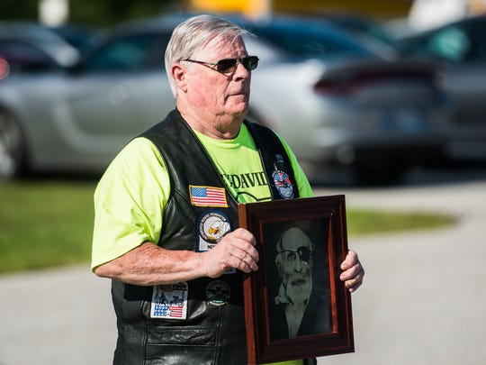 A member of Patriot Guard riders carries a portrait of Civil War veteran Pvt. Jewett Williams.