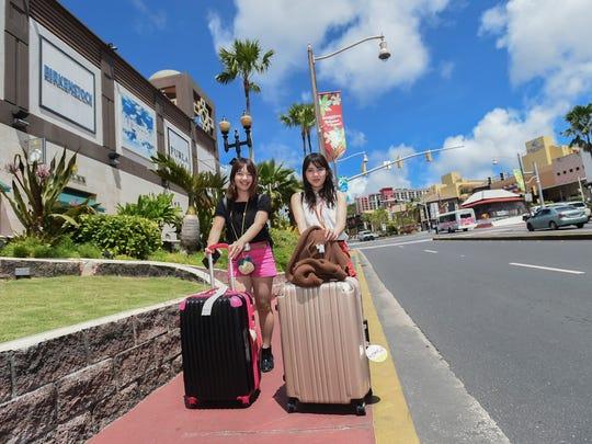 Travelers Miki Ueno, 22, right, and Yuki Motoi, 24,