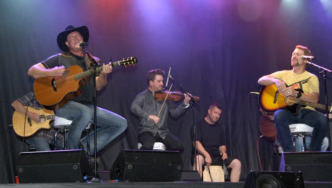 Tracy Lawrence (far left) performs Sunday evening on a Main Street stage in downtown Dickson for Craig Morgan's (far right) 8th annual charity concert for Billy's Place.