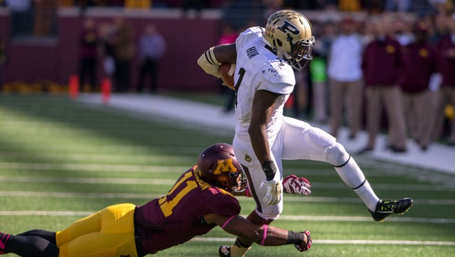 Purdue Boilermakers RB Akeem Hunt breaks away from tackle from Minnesota Golden Gophers defensive back Antonio Johnson (11) for a first down in the first half at TCF Bank Stadium.