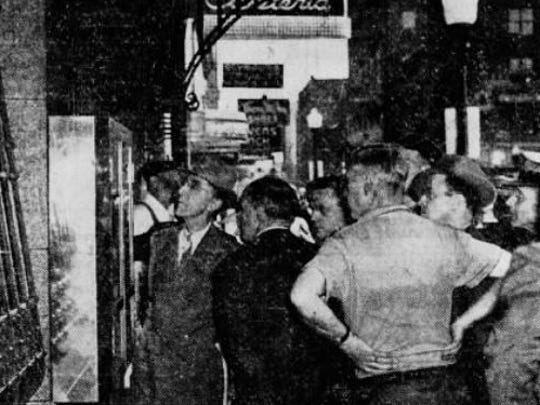 "In this photo from the June 5, 1943 Des Moines Register, a crowd quickly gathered in front of the Register and Tribune building as news spread of the death of Nile Kinnick, former Iowa Hawkeyes football all-American. The caption read: ""Their expressions tell how the death of Kinnick, when his plane crashed into the sea, saddened these readers."""
